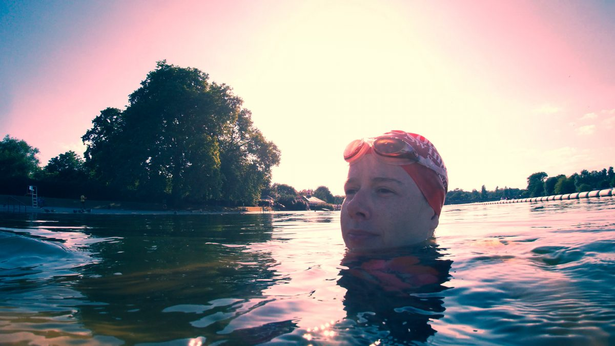 A woman swimming in water up to her face, with goggles and a swimming cap on, looking past the camera.