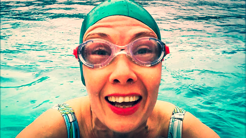 A female swimmer smiling at the camera