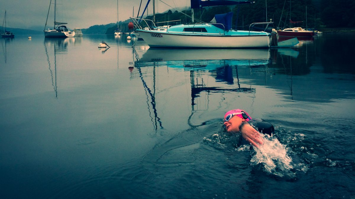 A swimmer in a wetsuit swimming past boats