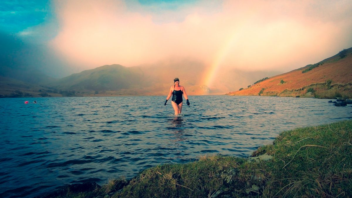A women swimmer walks out of a lake, with a rainbow and hills in the background