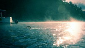 A swimmer raises their arm. Morning light reflects off the water, and mist rises up.