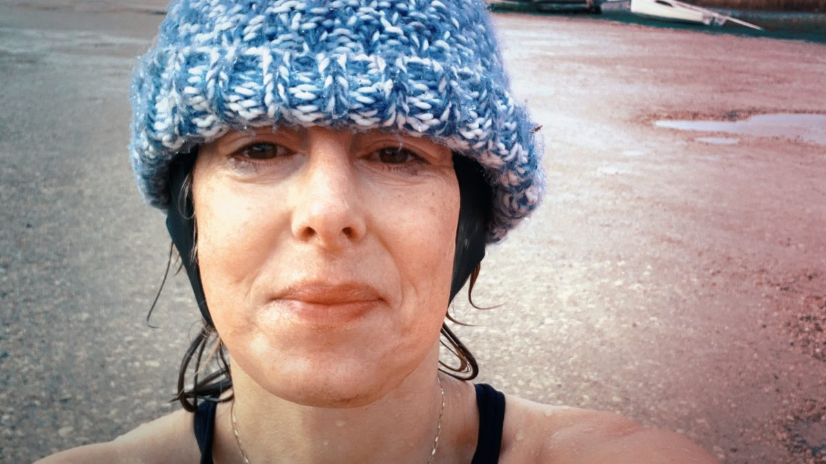 A woman wearing a blue bobble hat, after going swimming