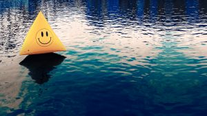 Floating on the water is a yellow buoy shaped like a triangle, with a smiley face in the middle